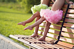 Little ballerinas legs. Two little girls wearing petit skirts doing batmant on the bench in the park Stock Images