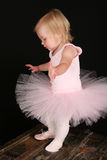 Little ballet girl. Cute little blond girl wearing a tutu and one ballet shoe Royalty Free Stock Photography