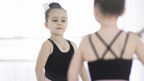 Little ballet girl in leotard are posing in front of the mirror