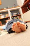 Little bare feet. Two little bare feet of a caucasian girl lying on the floor indoors (focus on feet stock photos