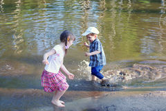Little barefoot girl with boy laugh and run in water of pond Royalty Free Stock Image