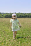 Little barefoot girl with flowers runs among grass Stock Photo