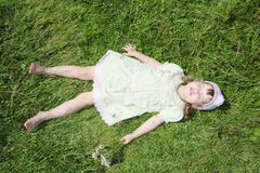 Little barefoot girl lies on green grass of meadow Stock Photography