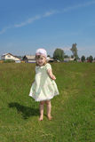 Little barefoot girl plays shows blade of grass Royalty Free Stock Photography