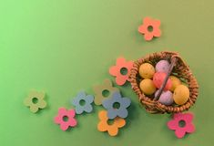 A little basket with easter eggs is standing on green background Royalty Free Stock Photography