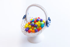 Little basket filled with  colorful candies. On white background Royalty Free Stock Image