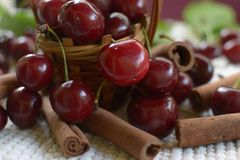 Little basket with handle, red cherries cinnamon rods on white. Little basket with handle red cherries with stems and leaf on white  tablecloth cinnamon rods Royalty Free Stock Photos