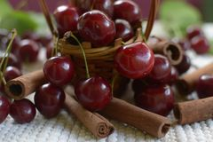 Red cherries with stems and cinnamon rods on white tablecloth Royalty Free Stock Photo