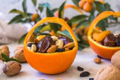 Little basket made of fresh orange filled with dry fruits; almonds, dates, raisins and nuts stock photos