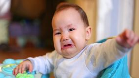 Little kazakh girl standing at home walker and crying unhappy baby stock footage