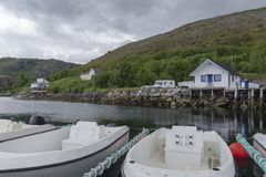Little bay in a fjord in Norway with boats in forefront. And a little village and mountains in background against a cloudy sky royalty free stock photography