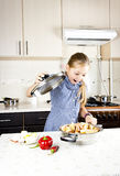 Little beatiful girl preparing food in the kitchen Stock Photos