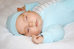 Little beautiful baby in blue jumper and hat sleeps Royalty Free Stock Photo