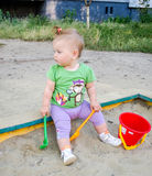 Little beautiful baby girl child plays bucket, rake and shovel in the sandbox sand Stock Image