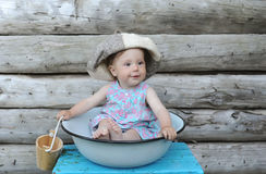 Little beautiful baby girl in washing-up bowl against the background of a wall of the wooden house.  Stock Image