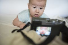 Little beautiful baby girl wondering looks at digital photocamera royalty free stock images