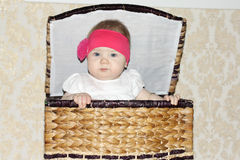 Little beautiful baby sits in big wicker basket Stock Photo