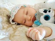 Little beautiful baby sleeps on a beige bed royalty free stock photo