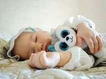Little beautiful baby sleeps on a beige bed royalty free stock images