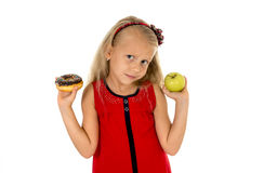Little beautiful blond child choosing dessert holding unhealthy chocolate donut and apple fruit royalty free stock photo