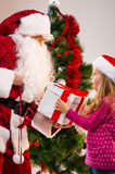 Little beautiful blond girl getting present from Santa Claus. Royalty Free Stock Photo