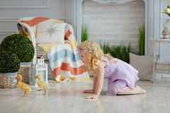 Little beautiful blond girl trying to grab ducks in a light stud. Io stock images