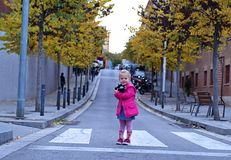 Cute Little photographer standing at a pedestrian crossing. Little beautiful blonde girl in a pink jacket, stands at a pedestrian crossing and holds a camera Royalty Free Stock Images