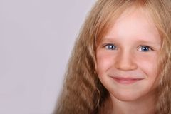 Little beautiful blonde smiling girl faces closeup. Royalty Free Stock Images