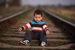 Little beautiful boy plays on railroad royalty free stock image