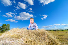 Little beautiful boy sitting on a pile of hay on a sunny day Royalty Free Stock Image