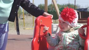 Little beautiful caucasian girl 3 years old plays with her mother in a modern playground for children, spring swing stock video footage