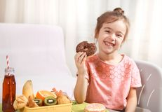 Little beautiful cheerful girl eating a donut. And lunch box with fruits at home at the table, the concept of children`s food royalty free stock photography