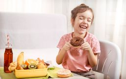 Little beautiful cheerful girl eating a donut stock images