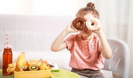 Little beautiful cheerful girl eating a donut royalty free stock image