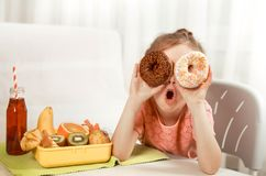 Little beautiful cheerful girl eating a donut stock image