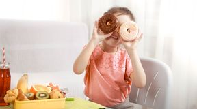 Little beautiful cheerful girl eating a donut royalty free stock images