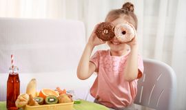 Little beautiful cheerful girl eating a donut stock photos