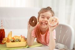 Little beautiful cheerful girl eating a donut royalty free stock photos