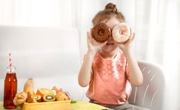 Little beautiful cheerful girl eating a donut royalty free stock photo