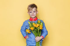 Little beautiful child with a bouquet of tulips. Son gives mom flowers on Women`s Day, Mother`s Day. Birthday. Valentine`s day. Sp Stock Photography