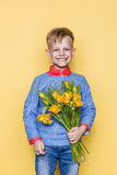Little beautiful child with a bouquet of tulips. Son gives mom flowers on Women`s Day, Mother`s Day. Birthday. Valentine`s day. Sp Royalty Free Stock Images