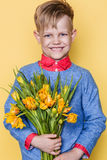 Little beautiful child with a bouquet of tulips. Son gives mom flowers on Women`s Day, Mother`s Day. Birthday. Valentine`s day. Sp. Little beautiful child with a royalty free stock photo