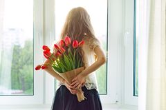 Little beautiful child girl with bouquet of red tulips flowers at home near the window, present for mother day. Gift, surprise, royalty free stock photo
