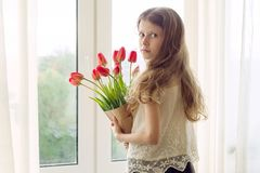 Little beautiful child girl with bouquet of red tulips flowers at home near the window, present for mother day. Gift, surprise, royalty free stock images