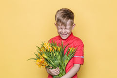 Little beautiful child with pink shirt gives a bouquet of flowers on Women`s Day, Mother`s Day. Birthday. Valentine`s day. Spring. Stock Photos