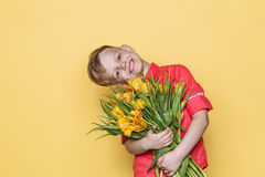 Little beautiful child with pink shirt gives a bouquet of tulips on Women`s Day, Mother`s Day. Birthday. Valentine`s day. Spring. Royalty Free Stock Image