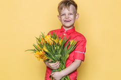 Little beautiful child with pink shirt gives a bouquet of tulips on Women`s Day, Mother`s Day. Birthday. Valentine`s day. Spring. Stock Images