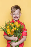 Little beautiful child with pink shirt gives a bouquet of tulips on Women`s Day, Mother`s Day. Birthday. Valentine`s day. Spring. Royalty Free Stock Photo
