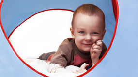 Little beautiful child playing. Hide smiles thinking Stock Photos