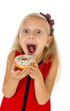 Little beautiful female child with long blonde hair and red dress eating sugar donut with toppings delighted and happy. Isolated on white background in children stock photography